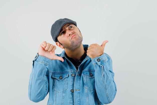 キャップ、tシャツ、ジャケットで親指を上下に見せて、ためらうように見える若い男。正面図。