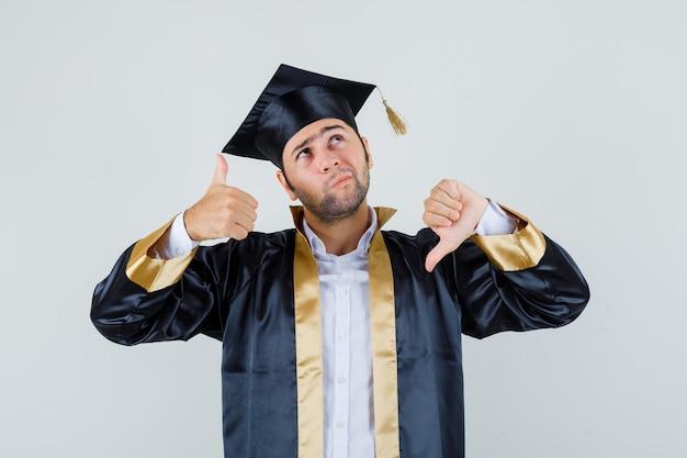 卒業式の制服を着て親指を上下に見せて躊躇している青年。正面図。