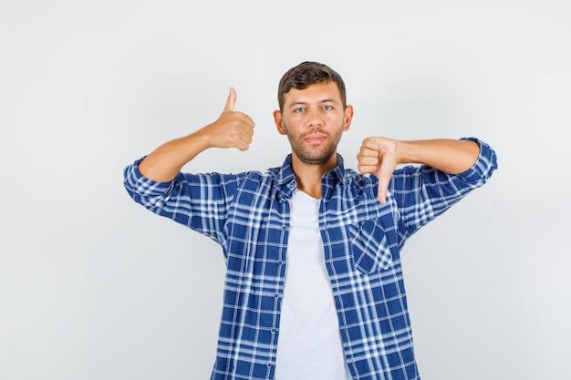 Молодой человек показывает большие пальцы руки вверх и вниз в рубашке и выглядит уверенно. передний план.