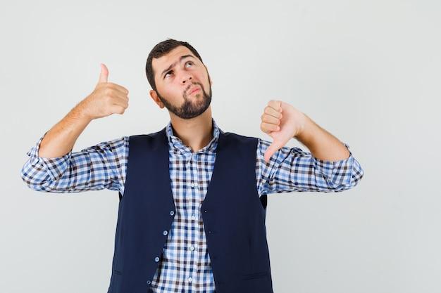 シャツ、ベストで親指を上下に見せて、ためらうように見える若い男。