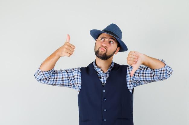 Молодой человек показывает большие пальцы руки вверх и вниз в рубашке, жилете, шляпе и выглядит нерешительным.