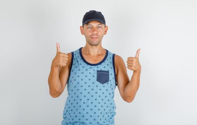 Молодой человек показывает палец вверх в синей майке с кепкой и выглядит счастливым