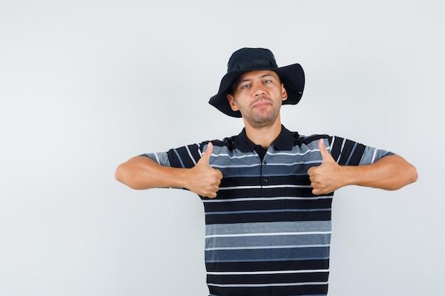 티셔츠, 모자를 쓰고 자신감을 보이는 젊은 남자가 앞모습을 보고 있습니다.