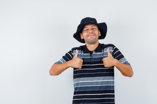 티셔츠, 모자를 쓰고 행복해 보이는 젊은 남자.