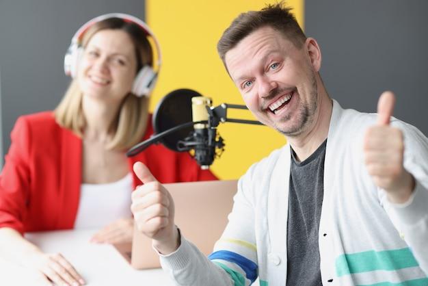 헤드폰과 마이크 라디오가 있는 라디오 진행자의 배경에 엄지손가락을 치켜드는 청년