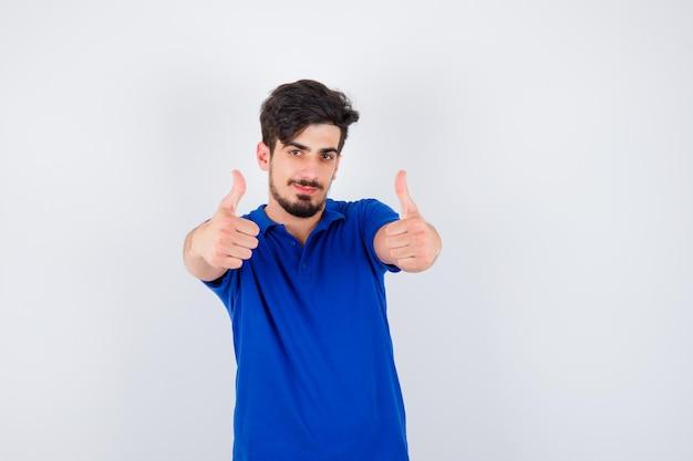 파란색 티셔츠에 양손으로 엄지 손가락을 보여주는 젊은 남자와 낙관적 찾고