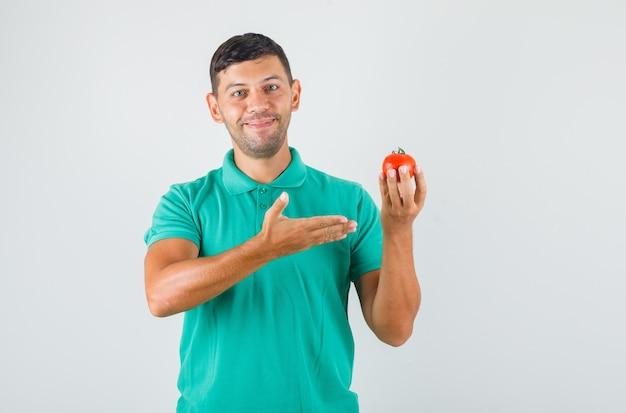 Giovane che mostra il pomodoro in mano in maglietta verdastra e sembra felice.