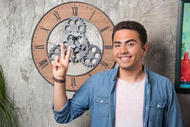 2本の指を上に表示し、大理石の背景にポーズをとる若い男。高品質の写真