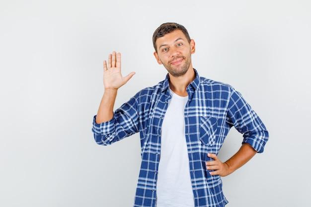 Молодой человек показывает ладонь с рукой на талии в рубашке и выглядит веселым. передний план.