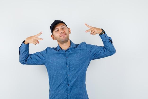 青いシャツ、キャップ、幸せそうに見える、正面図で勝利のサインを示す若い男。