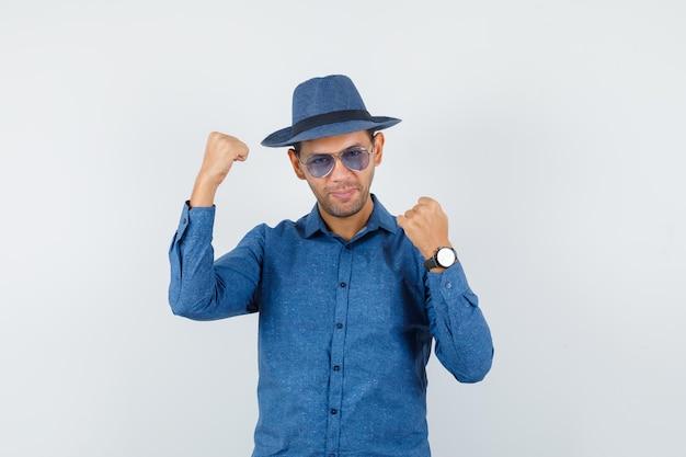 Молодой человек показывает жест победителя в голубой рубашке, шляпе и выглядит счастливым. передний план.