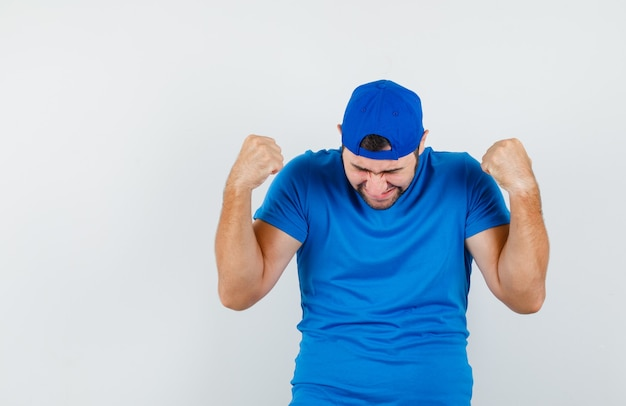 青いtシャツとキャップで勝者のジェスチャーを示し、感謝している若い男