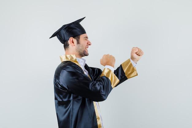 卒業式の制服を着て勝者のジェスチャーを示し、幸運に見える若い男。 。