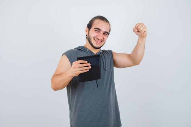 パーカーで勝者のジェスチャーを示し、幸せそうに見える若い男、正面図。