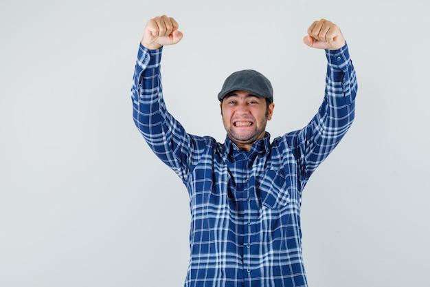 젊은 남자 셔츠, 모자에 우승자 제스처를 보여주는 행복, 전면보기.