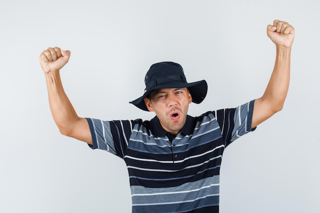 Молодой человек показывает жест победителя в футболке, шляпе и выглядит счастливым. передний план.