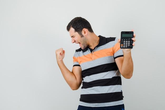 Tシャツに電卓を持って陽気に見えながら勝者のジェスチャーを示す若い男。正面図。
