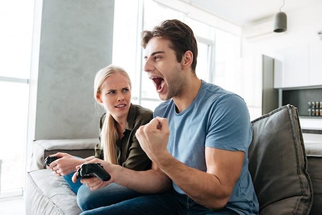 ビデオゲームで彼の女性と遊んでいる間若い男の勝者ジェスチャーを示す