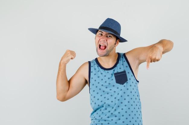 Молодой человек показывает жест победителя пальцем вниз в синей майке, шляпе и блаженным видом спереди.