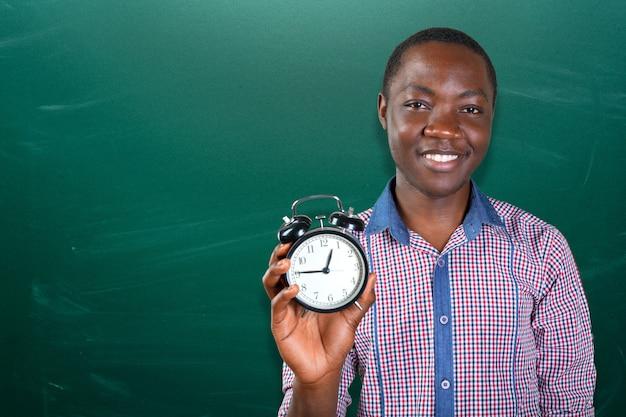 Молодой человек показывает вам будильник