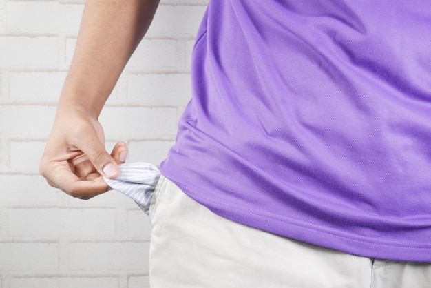 Young man shows empty pant pocket with copy space