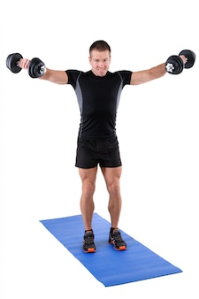 Young man shows finishing position of dumbbell lateral raise