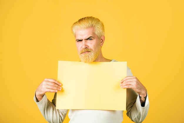 Young man shows a sheet of paper in the camera on a color background copy space