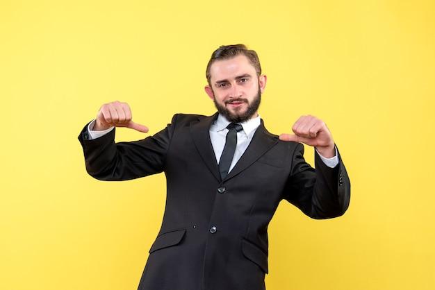 若い男は黄色の上に立っている間親指を下に表示します