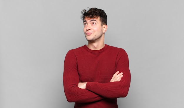 Young man shrugging, feeling confused and uncertain, doubting with arms crossed and puzzled look