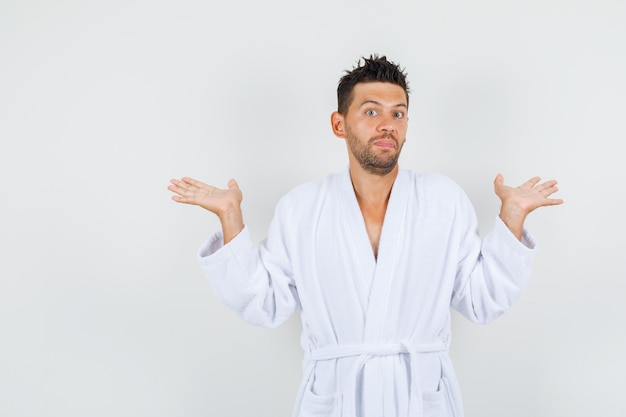 Young man shrugging and showing helpless gesture in white bathrobe , front view.