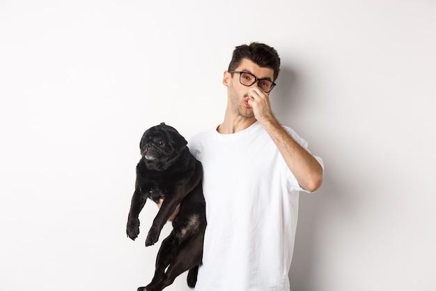 若い男はパグを持って鼻を閉じ、動物の悪臭のおならにうんざりし、白の上に立っている