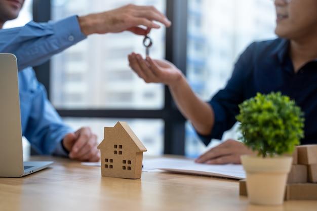 若い男が不動産業者のオフィスでの接触住宅購入またはレンタルに署名し、オフィスの若いカップルに新しい家からキーを与える販売担当者