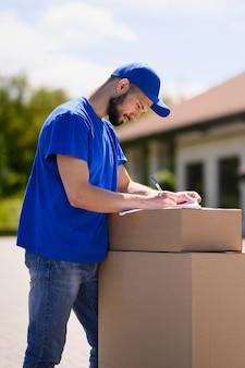 Young man signing delivery papers