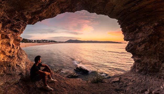 Силуэт молодого человека в прибрежной пещере рядом с пляжем хендая в стране басков.