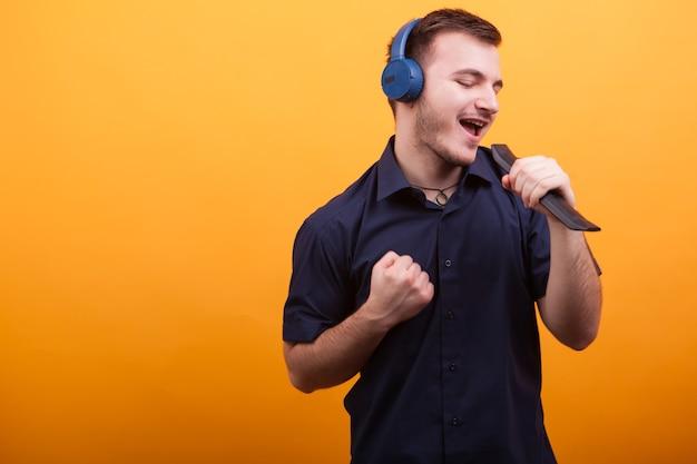 노란색 배경 위에 헤드폰을 끼고 기분 좋게 노래하는 젊은 남자. 훌륭한 음악.