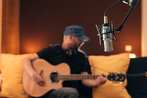 若い男が音楽スタジオで直接歌っています。
