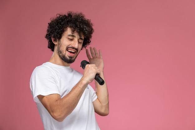 Молодой человек поет в микрофон