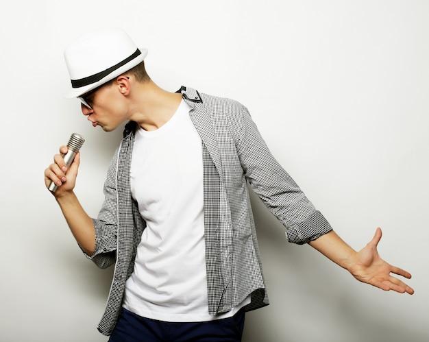Молодой человек поет с микрофоном