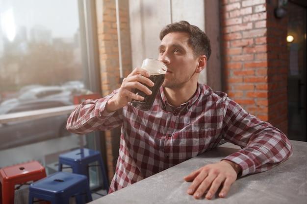 おいしいクラフトビールをすすりながら、ビールパブでリラックスした若い男、コピースペース