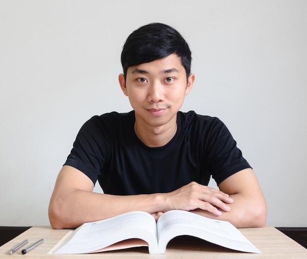 젊은 남자는 책을 들고 책상에 앉아 카메라 교육 개념을 보고 행복한 미소를 짓습니다.