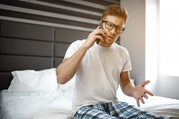 Young man sit on bed early morning. he talk on phone emotionally. guy work at home.