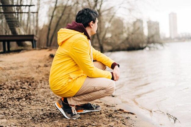 Молодой человек сидит на берегу озера на открытом воздухе на фоне осеннего парка