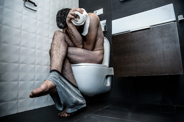 Young man sit on toilet in rest room