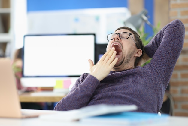 Young man siting at table in office and yawning. procrastination concept
