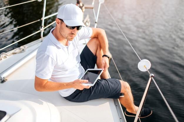 젊은 남자는 요트 보드의 가장자리에 앉아서 태블릿을 잡아. 남자는 셔츠와 선글라스와 흰색 모자를 착용. 그는 진지하고 자신감이 있습니다. 선원은 휴식을 취하십시오.