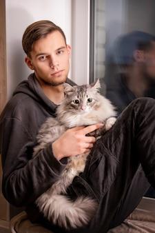 젊은 남자가 집에 창가에 앉아 소매에 뚱뚱한 솜털 고양이를 안고 있습니다.