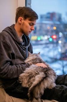 젊은 남자가 집 창가에 앉아 소매에 뚱뚱한 솜털 고양이를 안고