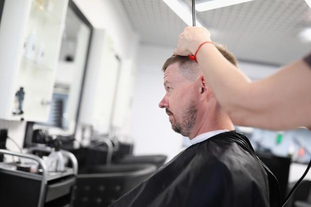 若い男は美容院の椅子に座って、美容院の肖像画で散髪をします
