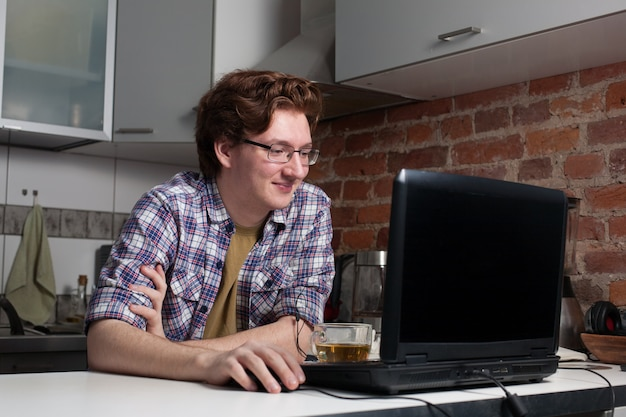 The young man sits at a laptop.