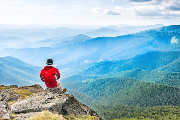 Young man sits and meditates on the top of mountain